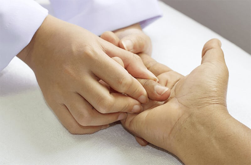 A hand therapist performing manual hands-on physical therapy